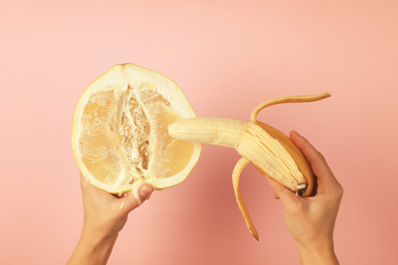Weibliche Hand hält eine Banane und Orange